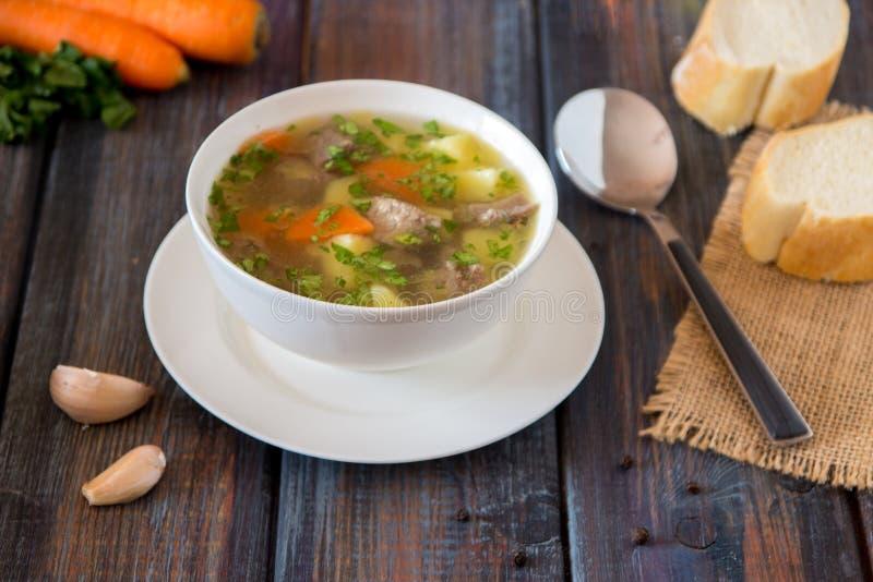 Sopa con la carne, las patatas y la zanahoria Sopa de la carne de vaca en un cuenco blanco fotos de archivo