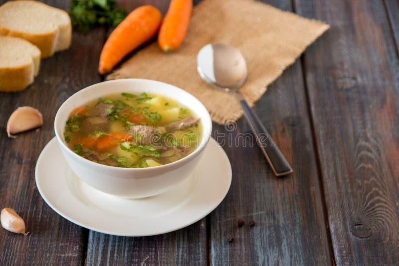 Sopa con la carne, las patatas y la zanahoria Sopa de la carne de vaca en un cuenco blanco, fotografía de archivo