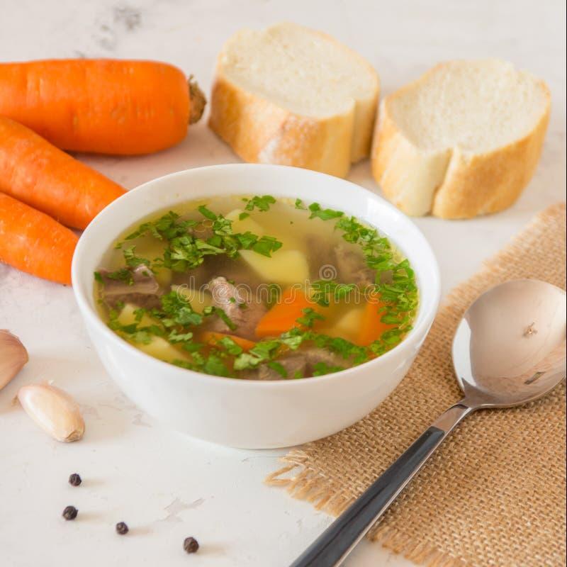 Sopa con la carne, las patatas y la zanahoria Sopa de la carne de vaca en un cuenco blanco imagen de archivo