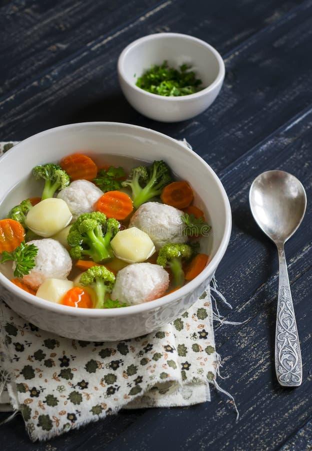 Sopa con las bolas de carne del pollo, las patatas, el bróculi y las zanahorias en un cuenco blanco imagen de archivo libre de regalías