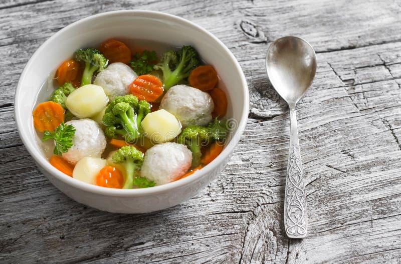 Sopa con las bolas de carne del pollo, las patatas, el bróculi y las zanahorias en un cuenco blanco imagen de archivo