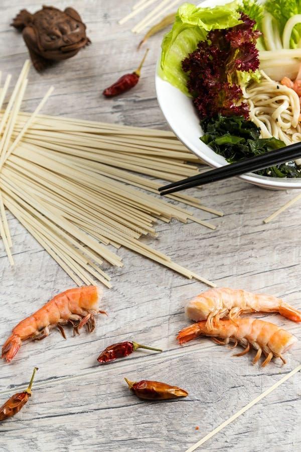 Sopa con los mariscos, los tallarines y las verduras en una placa blanca fotografía de archivo libre de regalías