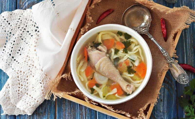 Sopa con los tallarines hechos en casa y el pollo orgánico con las zanahorias, raíz y hojas de los palillos del perejil, de la ce fotografía de archivo libre de regalías