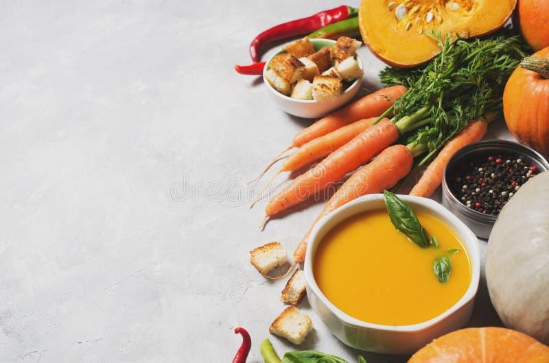 Sopa cremosa das abóboras com os vegetais sobre a textura cinzenta foto de stock royalty free
