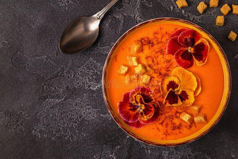 Sopa da abóbora/cenoura com açafrão e o amor perfeito comestível das flores foto de stock royalty free