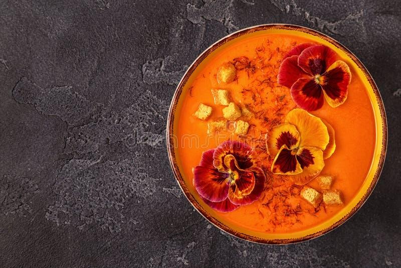 Sopa da abóbora/cenoura com açafrão e o amor perfeito comestível das flores fotografia de stock royalty free