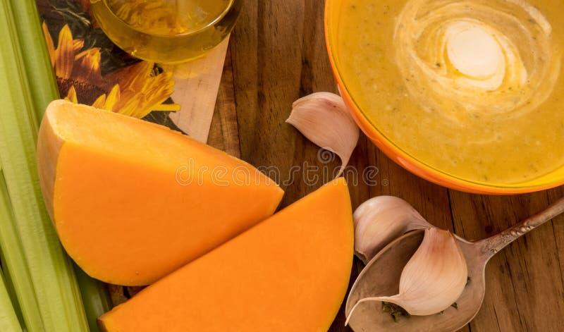 Sopa da abóbora e da cenoura com creme e salsa na tabela de madeira escura com selery, garlick e partes de abóbora imagens de stock