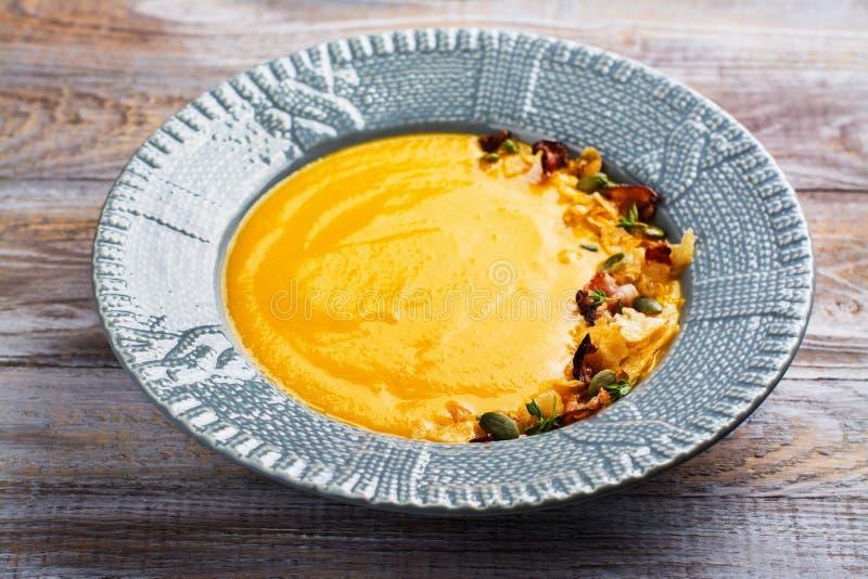 A sopa da abóbora e da cenoura serviu com sementes de abóbora, microplaquetas de batata foto de stock royalty free