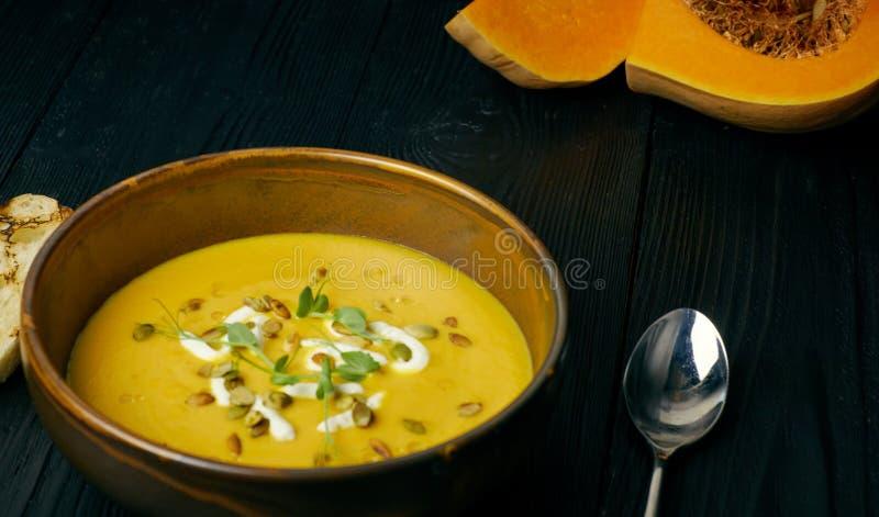 Sopa da abóbora em uma bacia com as sementes do creme e de abóbora Sopa do vegetariano Fundo de madeira escuro fotografia de stock