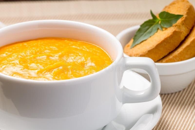 Sopa da abóbora em uma bacia com manjericão fresca foto de stock