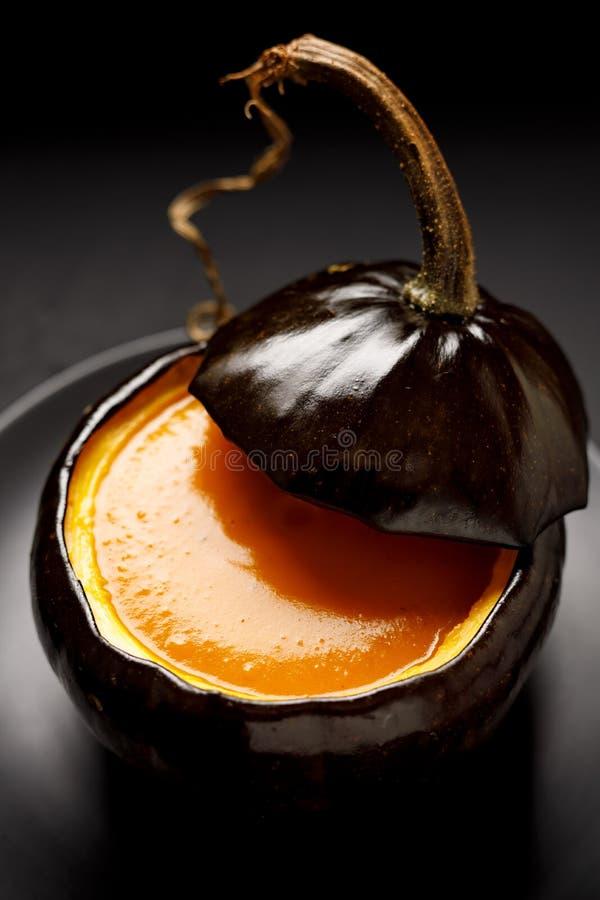 A sopa da abóbora serviu em uma abóbora oca cozida em um fundo preto fotografia de stock royalty free