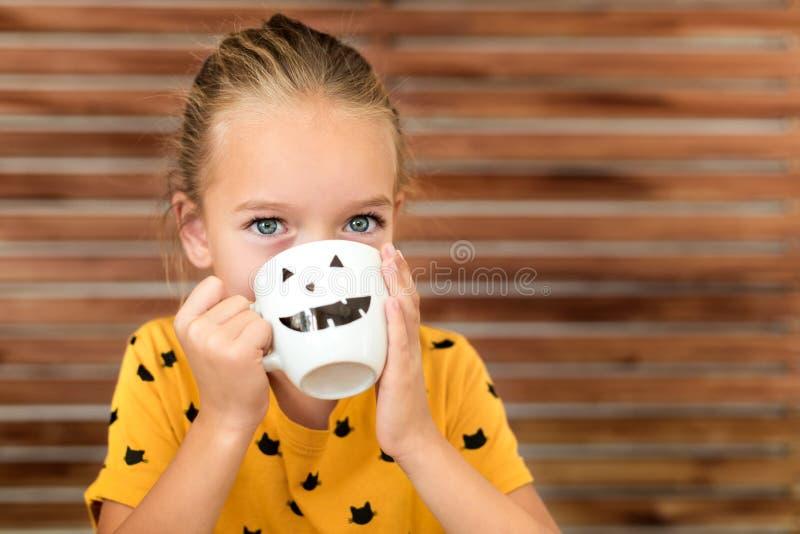 Sopa de consumición de la calabaza de la niña linda fuera de una taza con la cara sonriente antropomorfa de Halloween Comida de l imagen de archivo