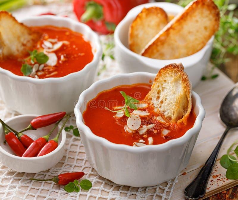 Sopa de crema de pimienta asada con la adición de almendros, pimientos de ají, hierbas frescas y tostadas en un tazón blanco de c imagenes de archivo