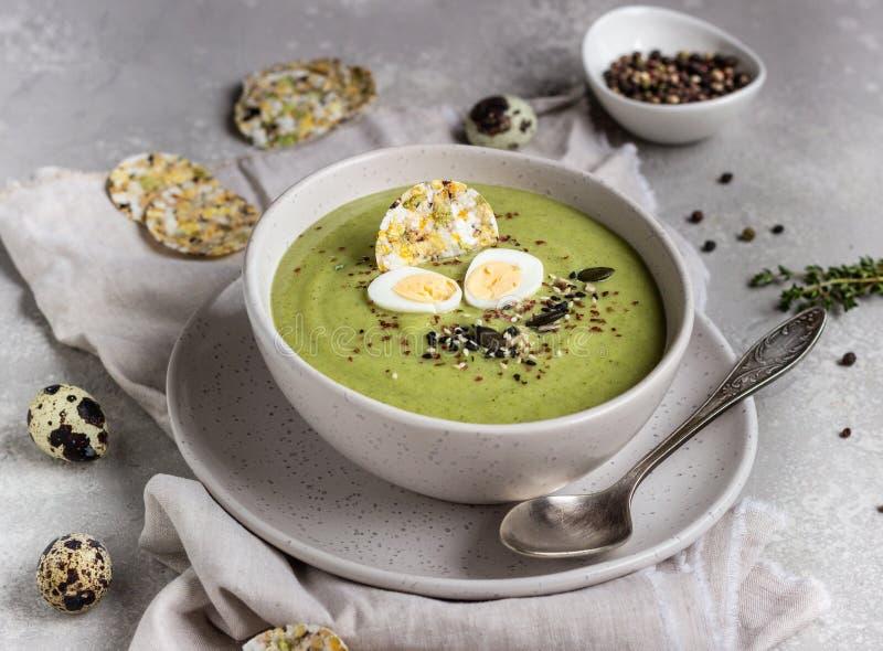 Sopa de crema verde de brócoli con mezcla de semillas, huevo de codorniz y galletas en cuenco sobre fondo gris claro fotografía de archivo libre de regalías