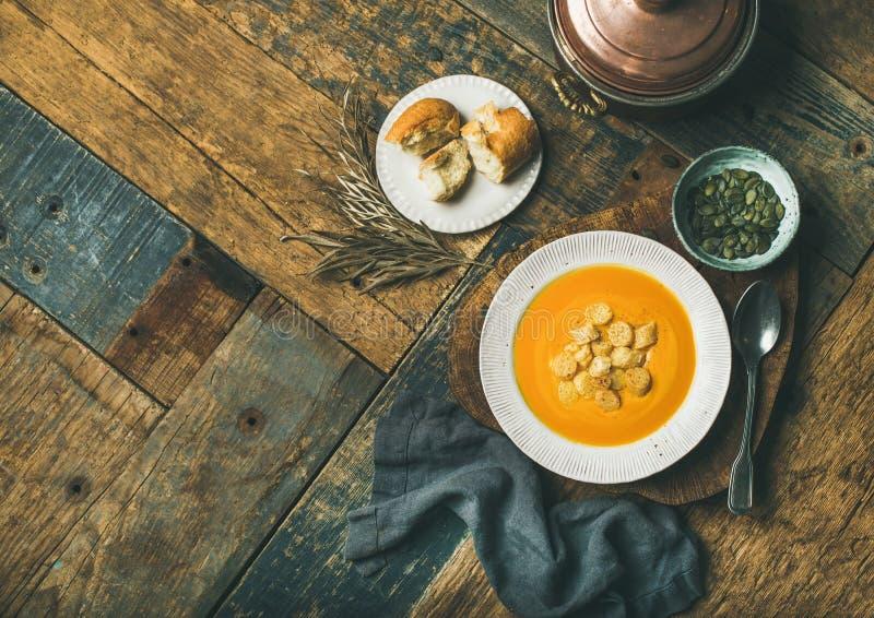 A sopa de creme de aquecimento da abóbora com pão torrado e sementes, copia o espaço imagens de stock