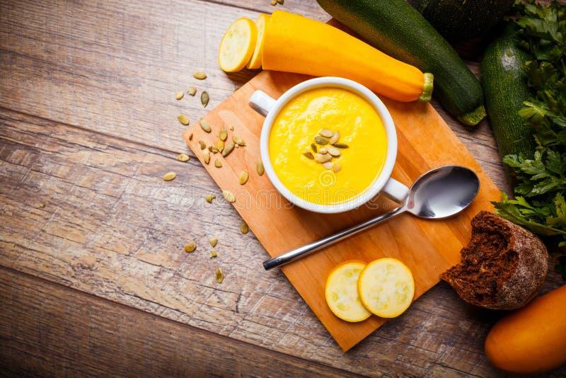 A sopa de creme da abóbora serviu com sementes e o pão torrado roasted em um fundo de madeira Conceito do alimento imagem de stock