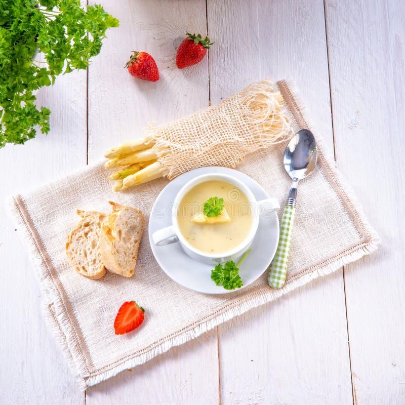 Sopa de creme do aspargo com alcaparras e o baguette fresco fotografia de stock royalty free