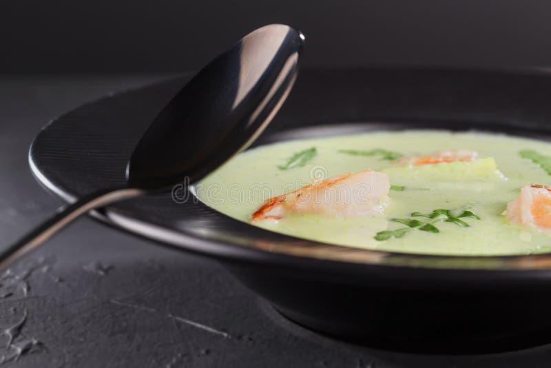 Sopa de creme dos brócolis do close-up com camarão em uma placa preta bonita em um fundo escuro Prato do marisco Foco seletivo fotografia de stock royalty free