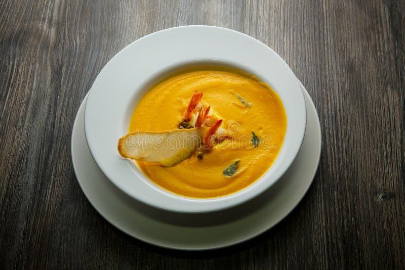 sopa de creme dos peixes frescos decorada com caudas dos camarões e uma fatia de pão secado foto de stock