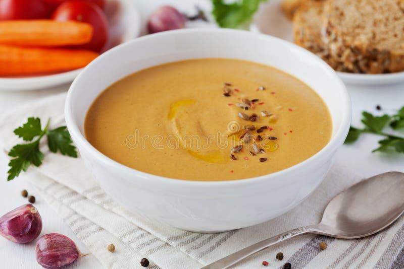 Sopa de creme vegetal do vegetariano com beringela e cenouras na bacia branca na tabela de madeira fotografia de stock royalty free