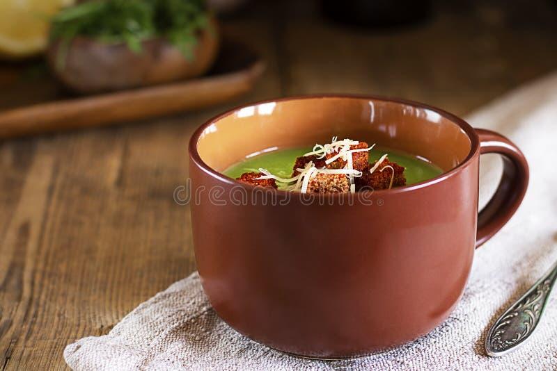 Sopa de creme verde com pão torrado vermelho e queijo raspado na caneca marrom no ctoth natural em ângulo da tabela de madeira rú fotografia de stock royalty free
