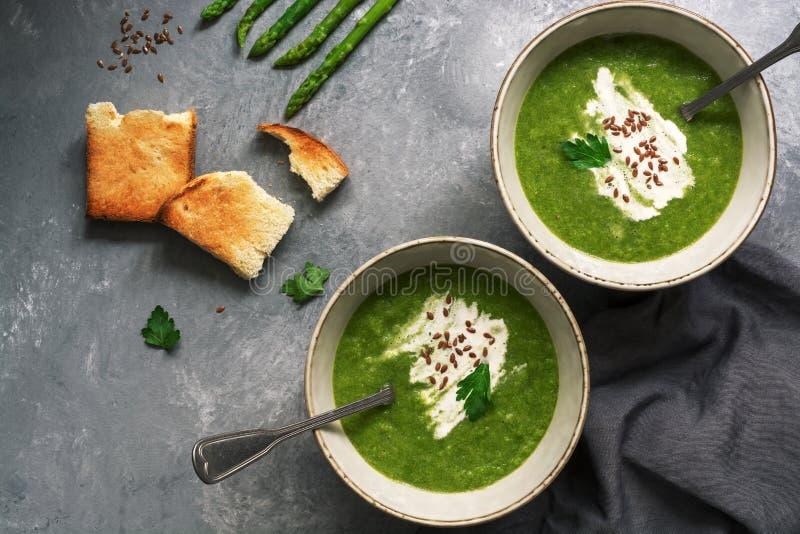 Sopa de creme verde do aspargo com brindes fri?veis em um fundo cinzento Vista a?rea, espa?o da c?pia foto de stock