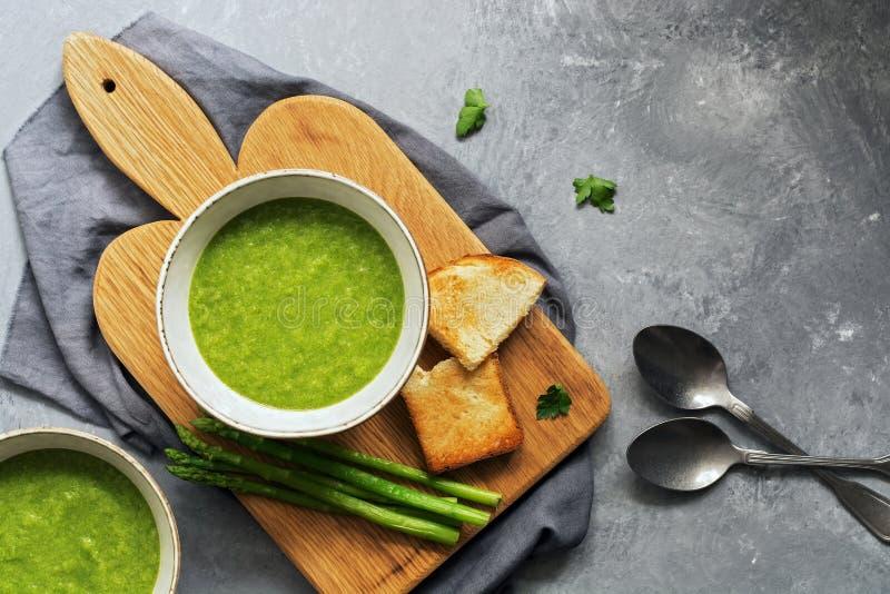 Sopa de creme verde do aspargo em uma placa de corte com brinde, fundo cinzento Vista superior, espa?o da c?pia, configura??o lis imagens de stock