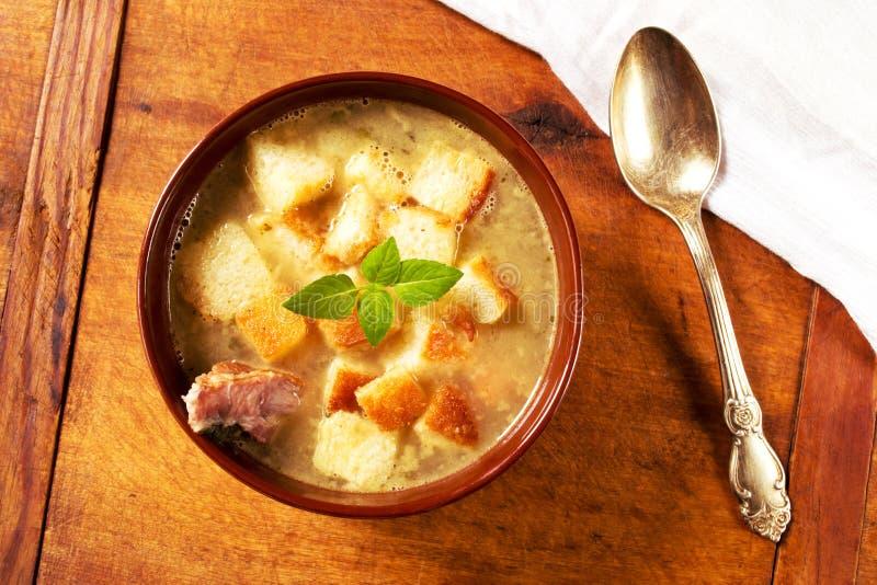 Sopa de ervilha deliciosa com reforços fumado e pão torrado foto de stock
