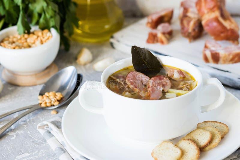 Sopa de ervilha grossa com carnes fumados em uma placa branca fotos de stock royalty free