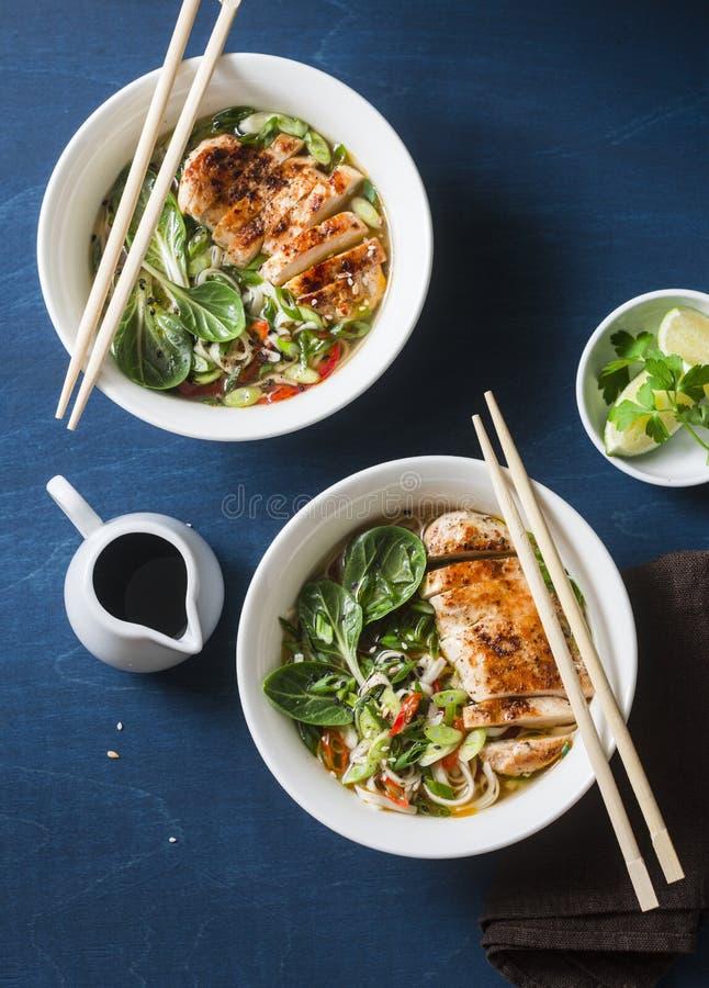 Sopa de fideos picante del udon del estilo asiático con el pollo frito en un fondo azul imagen de archivo libre de regalías