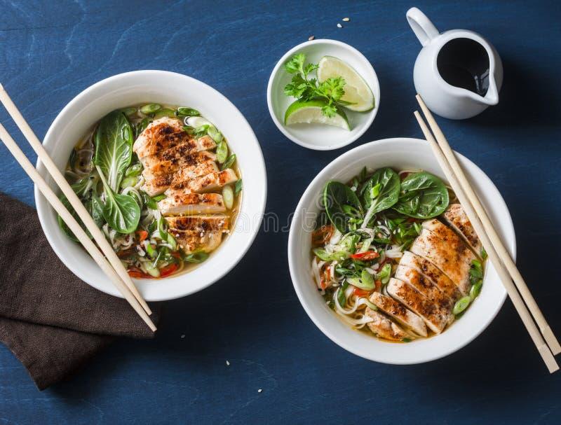 Sopa de fideos picante del udon del estilo asiático con el pollo frito en un fondo azul foto de archivo libre de regalías