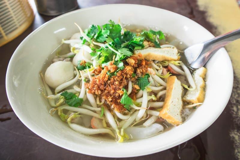 Sopa de fideos tailandesa en el cuenco blanco en la tabla foto de archivo