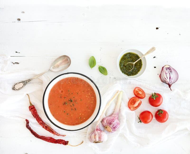 Sopa de Gazpacho en cuenco rústico del metal con los tomates frescos, la salsa verde, el chile, el ajo y la albahaca fotos de archivo libres de regalías