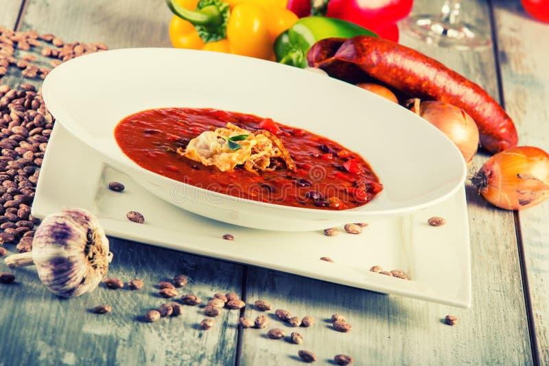 Sopa de habas - la cebolla decorativa de la pimienta del ajo de la salchicha derramó habas foto de archivo libre de regalías