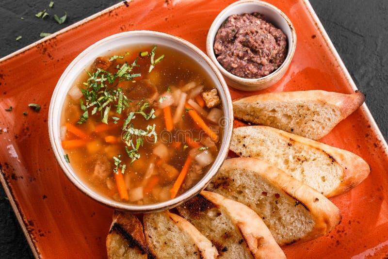 Sopa de habas vegetal con las hierbas en cuenco con los cuscurrones en fondo de piedra oscuro Comida sana del vegano imagenes de archivo