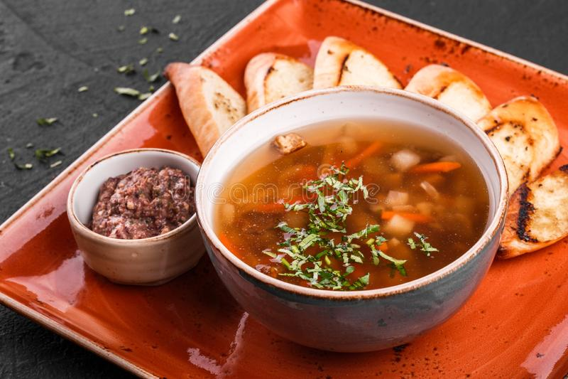 Sopa de habas vegetal con las hierbas en cuenco con los cuscurrones en fondo de piedra oscuro Comida sana del vegano fotografía de archivo libre de regalías