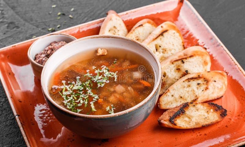 Sopa de habas vegetal con las hierbas en cuenco con los cuscurrones en fondo de piedra oscuro Comida sana del vegano Visi?n super imagen de archivo