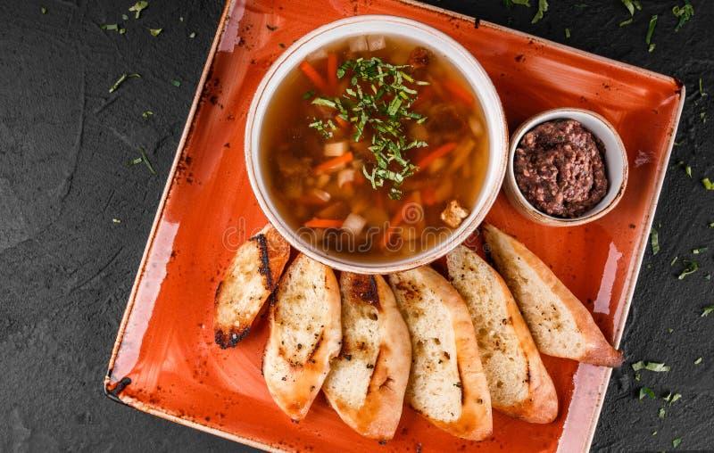 Sopa de habas vegetal con las hierbas en cuenco con los cuscurrones en fondo de piedra oscuro Comida sana del vegano Visi?n super fotografía de archivo libre de regalías