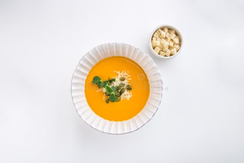 Sopa de la calabaza con las semillas de la crema y de calabaza y los cuscurrones aislados en el fondo blanco imagen de archivo