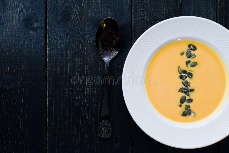 Sopa de la calabaza con las semillas en una placa blanca en un fondo negro imagenes de archivo