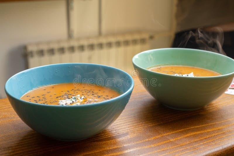 Sopa de la calabaza con queso cremoso y sésamo negro en el cuenco azul y verde que come para el concepto sano de la comida dos Ju fotografía de archivo libre de regalías