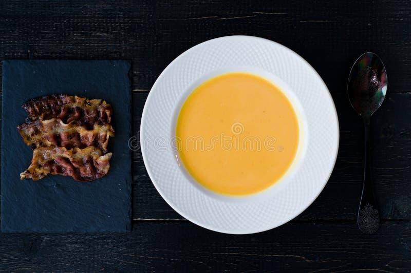 Sopa de la calabaza con tocino frito en la placa blanca en fondo negro foto de archivo