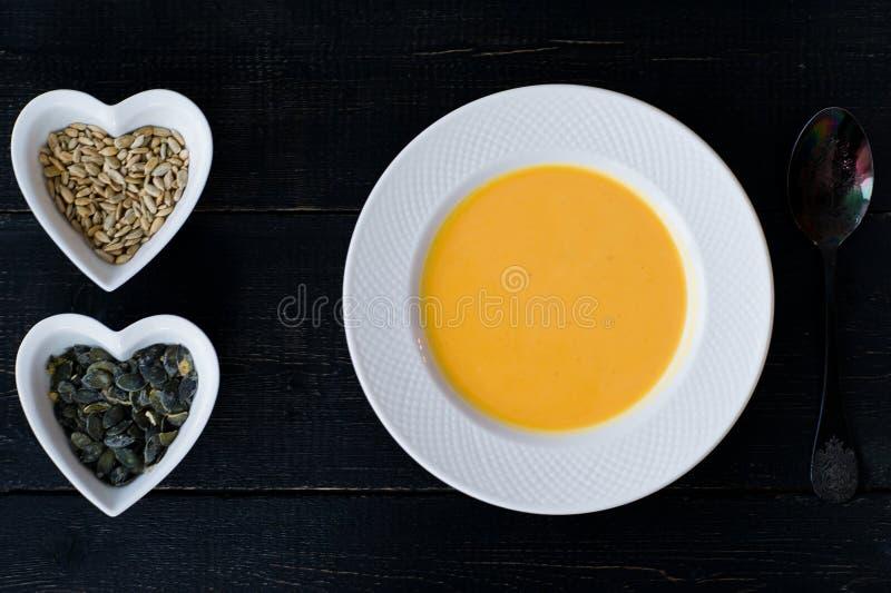 Sopa de la calabaza en la placa blanca en fondo negro fotografía de archivo libre de regalías