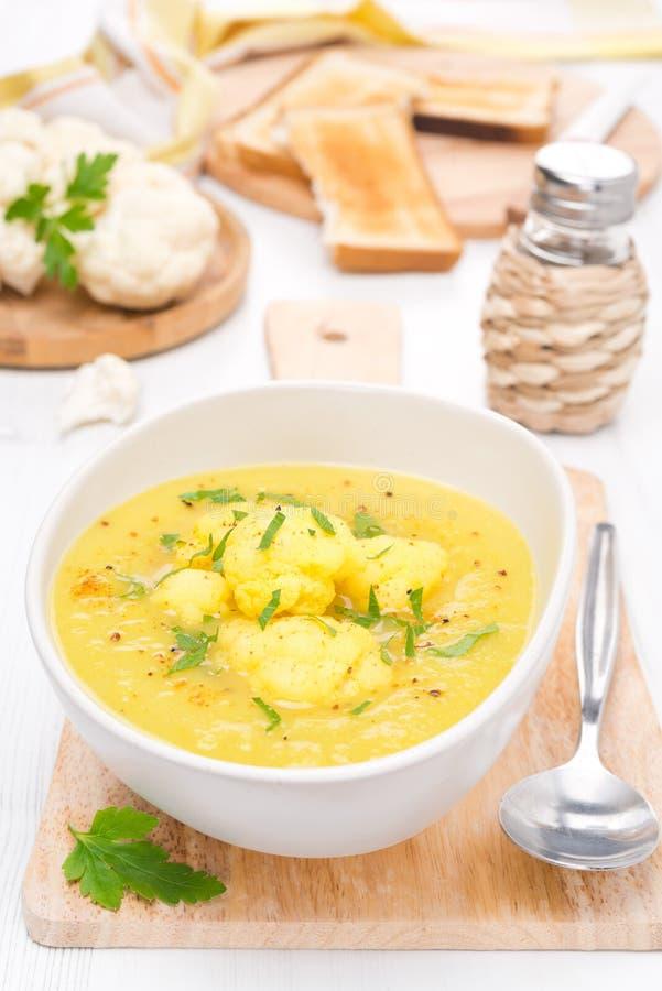 Sopa de la coliflor con curry en un cuenco fotografía de archivo