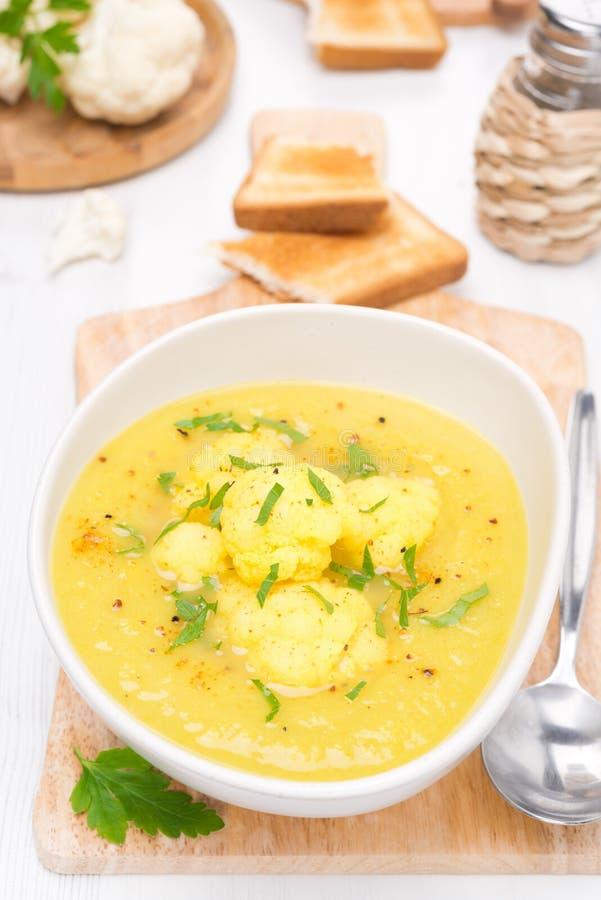 Sopa de la coliflor con el curry en un cuenco, visión superior foto de archivo