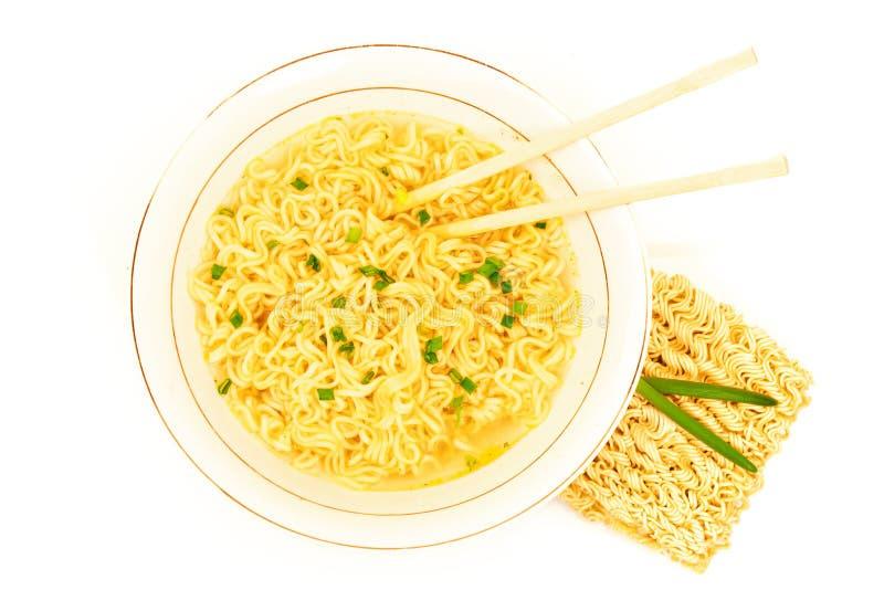 Sopa de la comida rápida en la placa con la cebolla verde, los palillos y los tallarines inmediatos de los ramen crudos crudos fotografía de archivo
