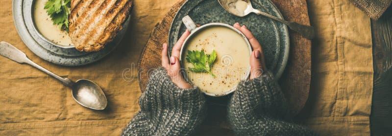 Sopa de la crema del apio, pan asado a la parrilla y manos femeninas, composición ancha imagen de archivo libre de regalías