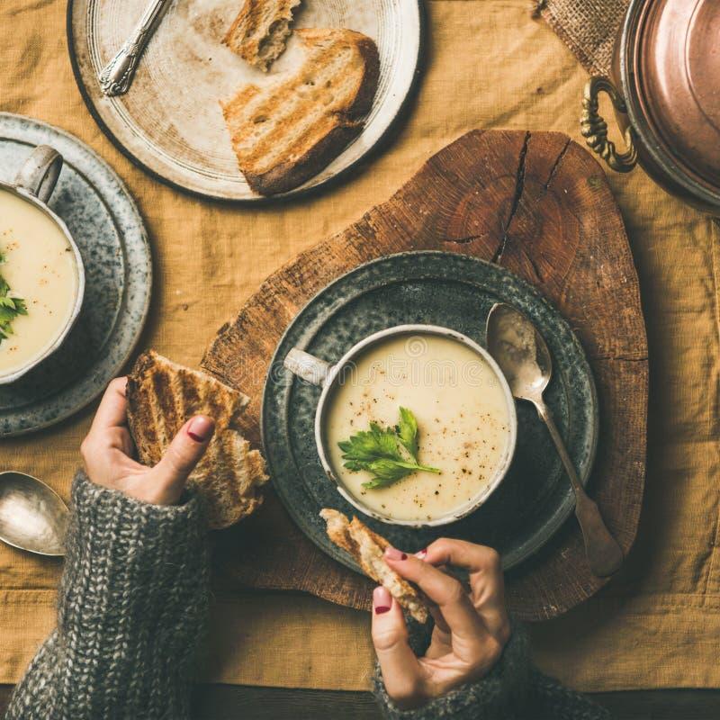 Sopa de la crema del apio y manos femeninas con el pan, cosecha cuadrada imagen de archivo libre de regalías
