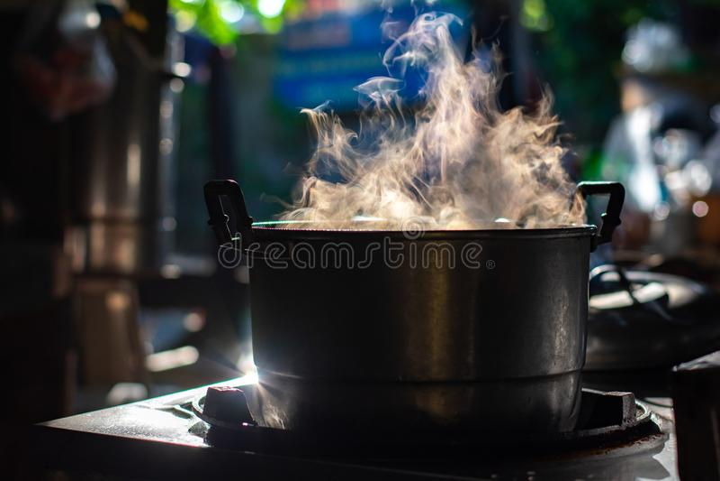 Sopa de la ebullición del pote del metal en estufa de gas con humo en cocina tailandesa Haga la comida para el desayuno imagenes de archivo