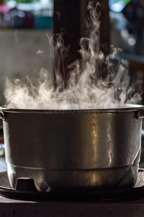 Sopa de la ebullición del pote del metal en estufa de gas con humo en cocina tailandesa Haga la comida para el desayuno imagen de archivo